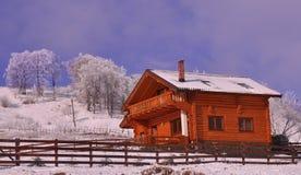 Nettes hölzernes Chalet in der winterlichen Landschaft Stockbild