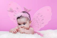 Nettes, hübsches, glückliches, molliges Baby neugierig über ihre Hände, die Augen kreuzen, um zu fokussieren Stockbild