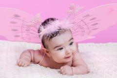 Nettes, hübsches, glückliches, molliges und lächelndes Baby, mit rosa Schmetterling beflügelt Lizenzfreies Stockbild