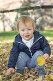 Nettes jähriges Baby, das auf Gras in einem Park sitzt stockfoto