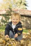 Nettes jähriges Baby, das mit Blättern an in einem Park spielt stockbilder