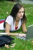 Nettes jugendlich Mädchen, das auf dem Grasstudieren niederlegt Stockfotografie