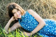 Nettes jugendlich Mädchen im blauen Kleid, das auf dem Bauernhof sitzt Lizenzfreies Stockbild