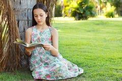 Nettes jugendlich Mädchenlesebuch, das auf grünem Gras sitzt Stockfotografie