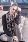 Nettes jugendliches blondes Mädchen, das draußen auf Treppe aufwirft Stockbilder