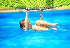 Nettes Jungenkind, das den Spaß, Bremsung auf Volleyballnetz machend im Pool hat Stockbilder