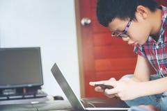 Nettes Jungenspielspiel im Handy und Betrachten des Laptops, Lizenzfreie Stockfotografie