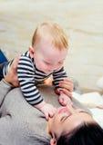 Nettes junges Baby, das mit seiner Mutter spielt Lizenzfreie Stockfotos