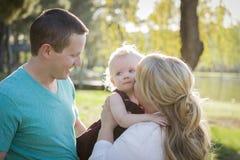 Nettes junges Baby, das von seinen Eltern umarmt wird Stockfotos