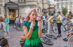 Nettes junges blondes Mädchen in den Weinlesekleidermalereilippen durch Lippenstift in der Menge des Festivals Stockfoto