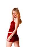 Nettes junges blondes Mädchen im roten Rock auf einer Weißrückseite Stockfotografie