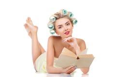 Nettes junges blondes Mädchen mit Lockenwicklern ist entspannend Lizenzfreie Stockfotos