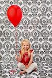 Nettes junges blondes Mädchen mit rotem Ballon Stockbilder