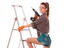 Nettes junges Brunetteerbauermädchen in der Uniform und in den Gläsern lässt Erneuerung mit ihre Hände herein bohren, die auf Wei stockfoto