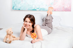 Nettes junges Brunettemädchen mit zwei Pyjamas Lügeno der Zöpfe zu Hause lizenzfreies stockfoto