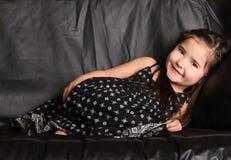 Nettes junges Kind, das auf einer Couch liegt lizenzfreie stockbilder