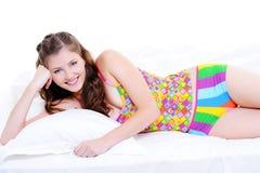 Nettes junges lächelndes Mädchen, das sich auf Bett hinlegt Stockfotos
