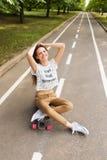 Nettes junges Mädchen, das auf einem longboard, gekreuzt ihren Armen über ihrem Kopf auf der Straße im Park sitzt skateboarding d Stockfotos