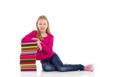 Nettes junges Mädchen, das auf Stapel Büchern sich lehnt Stockfoto