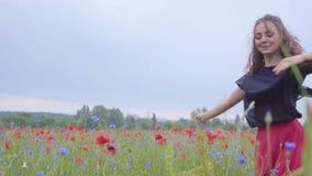 Nettes junges Mädchen, das in ein Mohnblumenfeld glücklich lächelt läuft und tanzt Verbindung mit Natur Freizeit in der Natur stock video footage