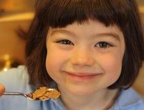 Nettes junges Mädchen, das Getreide isst Lizenzfreies Stockfoto
