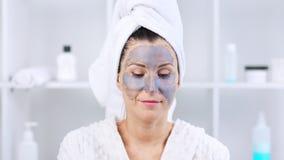 Nettes junges Mädchen, das graue Maske auf ihrem Gesicht macht stock footage