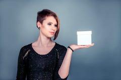 Nettes junges Mädchen, das Kasten auf einer Hand hält Lizenzfreie Stockbilder