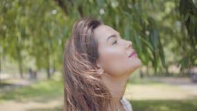 Nettes junges Mädchen des Porträts mit dem langen brunette Haar, das eine lange weiße Sommermode-Kleiderstellung unter den Nieder stock video footage