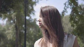 Nettes junges Mädchen des Porträts mit dem langen brunette Haar, das eine lange weiße Sommermode-Kleiderstellung unter den Nieder stock video