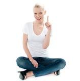 Nettes junges Mädchen gesetzt auf Fußboden und oben zeigen lizenzfreie stockfotos
