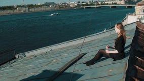 Nettes junges Mädchen im schwarzen Kleid, das auf Deckung mit szenischem Stadtbild sitzt stock video footage