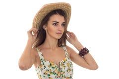 Nettes junges Mädchen im Sommer und in den Blicken in Richtung zu Sarafan hält Hand auf Hut Stockbild
