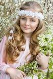 Nettes junges Mädchen mit dem langen blonden Haar, das in einer Wiese im Kranz von Blumen, einen Blumenstrauß des Frühlinges halt Lizenzfreie Stockfotografie