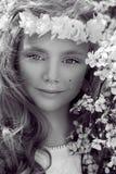 Nettes junges Mädchen mit dem langen blonden Haar, das in einer Wiese im Kranz von Blumen, einen Blumenstrauß des Frühlinges halt Lizenzfreies Stockbild