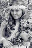 Nettes junges Mädchen mit dem langen blonden Haar, das in einer Wiese im Kranz von Blumen, einen Blumenstrauß des Frühlinges halt Lizenzfreie Stockfotos