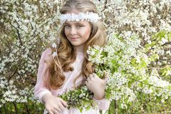 Nettes junges Mädchen mit dem langen blonden Haar, das in einer Wiese im Kranz von Blumen, einen Blumenstrauß des Frühlinges halt Stockfotos