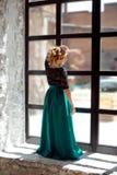 Nettes junges Mädchen mit den geschlossenen Augen, die zu Hause nahe dem Fenster stehen und warmes Sonnenlicht genießen Stockfoto