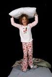 Nettes junges Mädchen mit Kissen auf ihrem Kopf Stockbilder