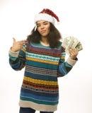 Nettes junges Mädchen in rotem Hut Sankt mit dem Geld lokalisiert Lizenzfreies Stockfoto