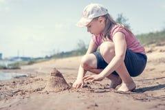 Nettes junges M?dchen, das Spa? auf einem sandigen Seestrand am warmen und sonnigen Sommertag hat Junges M?dchen, das durch den F stockfotografie