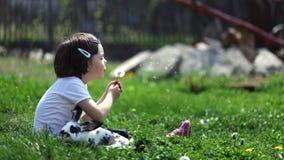 Nettes junges Mädchen mit dem Kaninchen, das einen Löwenzahn durchbrennt Stockfotos