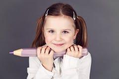 Nettes junges Schulmädchen, das einen Bleistift hält stockfotos