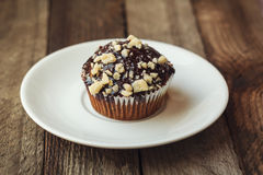 Nettes köstliches süßes Muffin mit Schokolade auf hölzernem Hintergrund Stockfotografie