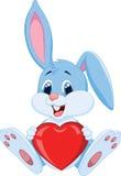 Nettes Kaninchen, das roten Hut hält Stockfotografie