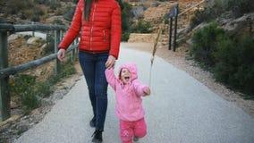 Nettes kaukasisches Baby in der Haube mit Kraut strow lachenden Läufen, die Mutter ` s halten, übergeben das Versuchen, die Kamer stock video footage