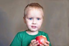 Nettes kaukasisches Baby mit blauen Augen und dem blonden Haar in grünem t-kurzem isst den roten Apfel und hält es auf den Händen stockbild