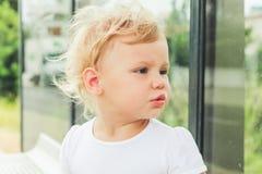 Nettes kaukasisches blondes Baby auf einer Bushaltestelle Stockbild