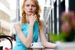 Nettes kaukasisches blondes Mädchen im blauen Kleid, das im Café sitzt Stockbild