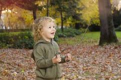 Nettes kaukasisches Kind, das im Park mit Stöcken spielt stockfoto