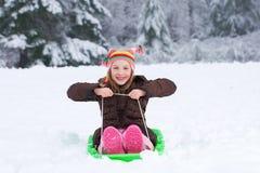 Nettes Kind auf einem Schneeschlitten Lizenzfreie Stockfotografie